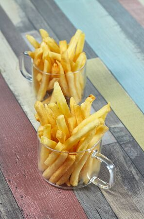 French fries are served in two glass mugs on a wooden surface painted in different colours. Imagens - 128615693