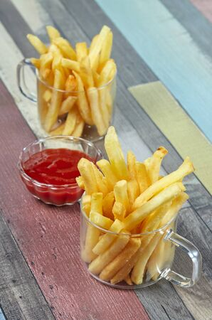 French fries are served in two glass mugs and a portion of ketchup, on a wooden surface painted in different colors. Imagens - 128615694