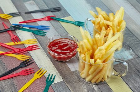 French fries are served in two glass mugs and portions of ketchup, on a wooden table top painted in different colors with decorative forks scattered on the surface. Imagens - 128615692