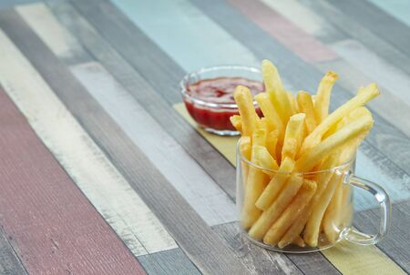 French fries are served in glass mugs and ketchup portion, on a wooden surface painted in different colors. Banco de Imagens