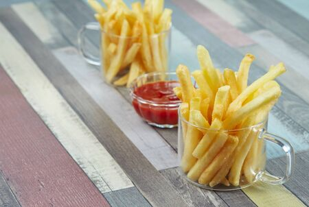 French fries are served in two glass mugs and a portion of ketchup, on a wooden surface painted in different colors. Diagonal composition. Imagens - 128615697