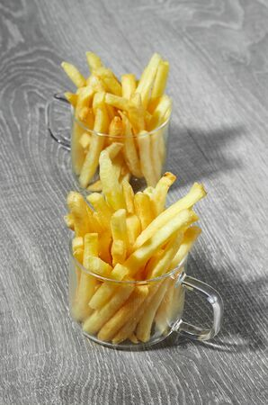 French fries are served in two glass mugs on a grey wooden surface. Imagens - 128615703
