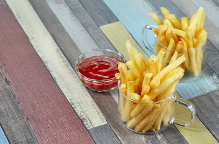 French fries are served in two glass mugs and a portion of ketchup, on a wooden surface painted in different colors. Imagens - 128615705