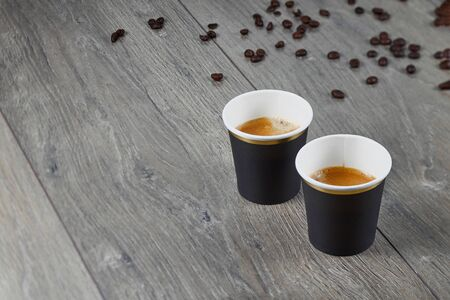 Two cups of espresso on a wooden background with coffee beans. Biodegradable packaging. Environmentally friendly material. Horizontal. Banco de Imagens