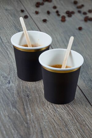 Two cups of espresso on a wooden background with coffee beans. Biodegradable packaging. Environmentally friendly material. Imagens