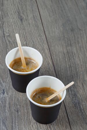 Two cups of espresso on a wooden background. Biodegradable packaging. Environmentally friendly material. Banco de Imagens