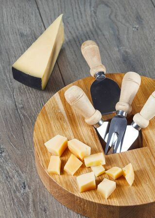 Cheese cutting Board with tools and cheese cubes on cheese sector background. Old tradition of cutting the cheese.