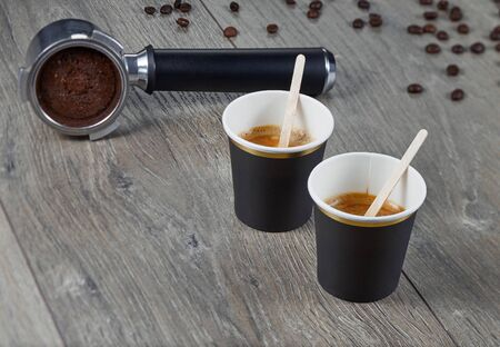 Two cups of espresso with chopsticks for blending on the background holder ground coffee. Biodegradable packaging. Environmentally friendly material.