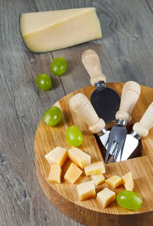 Cheese cutting Board with tools, cheese cubes and grapes on wooden table top background. Vertical. Imagens - 128615837