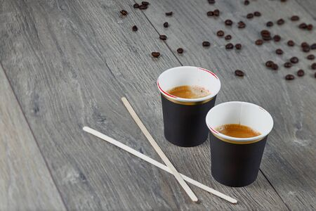 Two cups of espresso with mixing sticks on a wooden background with coffee beans. Environmentally friendly material.