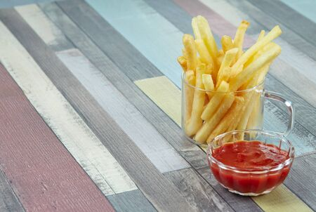 French fries are served in two glass mugs and a portion of ketchup, on a wooden surface painted in different colors. Copy space. Imagens