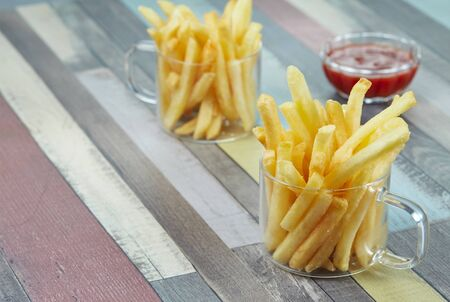 French fries are served in two glass mugs and a portion of ketchup, on a wooden surface painted in different colors. Horizontal. Imagens - 128615846