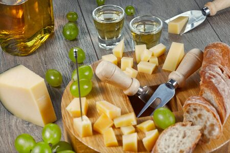 Grappa in small glasses with cheese, bread and grapes. Close-up of a simple rural meal in Italy. Close up.