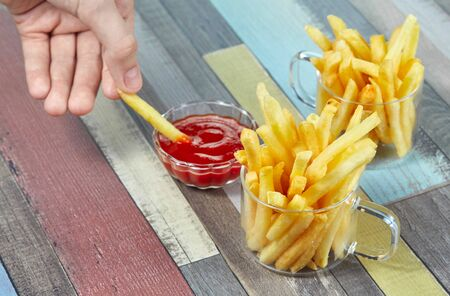 French fries serve in two glass mugs on a wooden surface painted in different colors. Imagens - 128615920