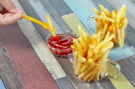 Hand dipping French fries in ketchup. French fries serve in two glass mugs on a wooden surface painted in different colors. Imagens