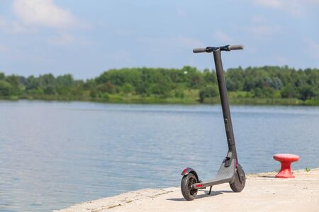 Modern electric scooter standing on the pier on the background of a picturesque river and forest. Environmentally friendly modes of transport. Banco de Imagens