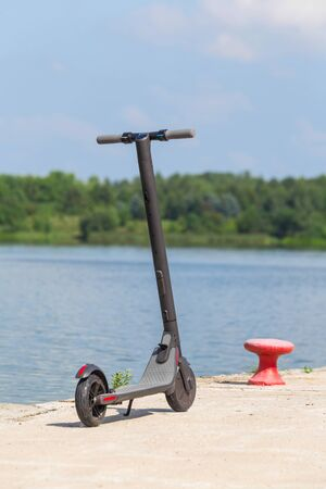 Modern electric scooter standing on the pier on the background of a picturesque river and forest. Environmentally friendly modes of transport. Imagens - 128615932