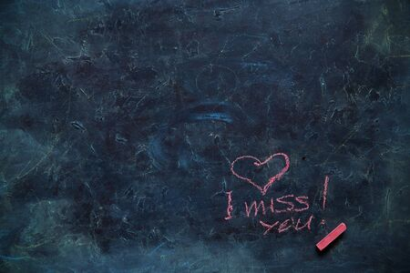 Dirty chalkboard with the inscription I MISS YOU and a small pink color. Blackboard with chalk doodle, can put more text at a later. Imagens