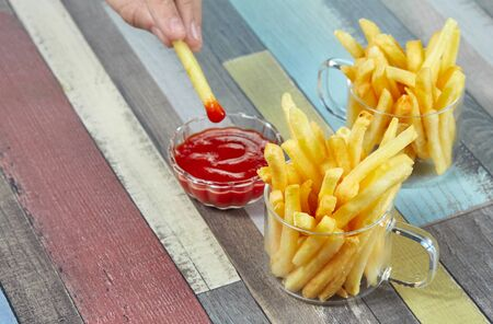 French fries are served in two glass mugs and a portion of ketchup, on a wooden surface painted in different colors. Imagens