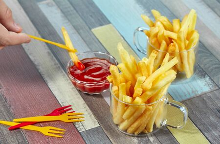 French fries are served in two glass mugs and portions of ketchup, on a wooden table top painted in different colors with decorative forks scattered on the surface.