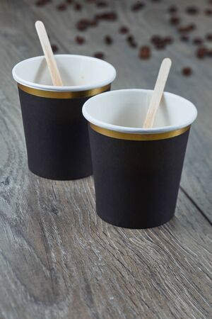 Two empty espresso cups on a wooden background with coffee beans. Biodegradable packaging. Environmentally friendly material. Imagens - 128615951