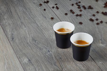 Two cups of espresso on a wooden background with coffee beans. Biodegradable packaging. Environmentally friendly material. Banco de Imagens