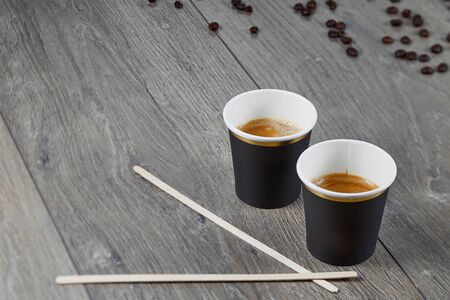 coffe paper cup beanTwo cups of espresso with mixing sticks on a wooden background with coffee beans. Biodegradable packaging. Environmentally friendly material. Imagens - 128615955