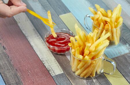 Hand dipping French fries in ketchup. French fries serve in two glass mugs on a wooden surface painted in different colors. Horizontal.