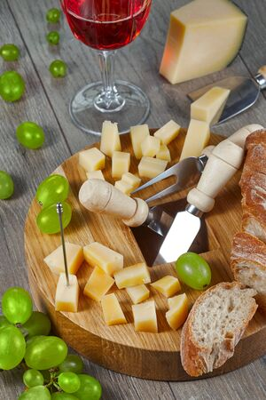 Cheese of different varieties, cut for tasting on a cutting Board with grapes, bread and a glass of red wine. Close up.