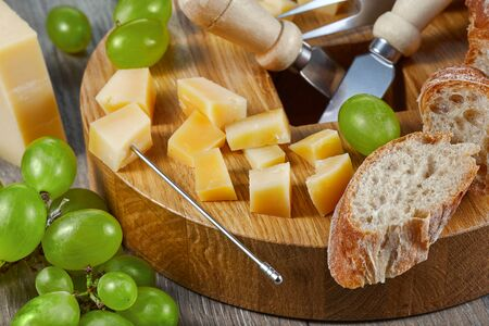 Close-up still life of pieces of cheese, grapes, bread and cheese cutting tools on the cutting Board. Horizontal.