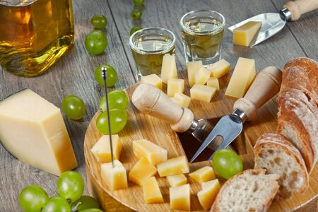 Cheese of different varieties, diced for tasting on a cutting Board with grapes, bread and Grappa. Close up. Imagens