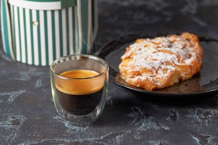 cup of coffee and croissant on dark table. Imagens