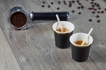 coffeTwo cups of espresso with chopsticks for blending on the background holder ground coffee. Biodegradable packaging. Environmentally friendly material. Horizontal