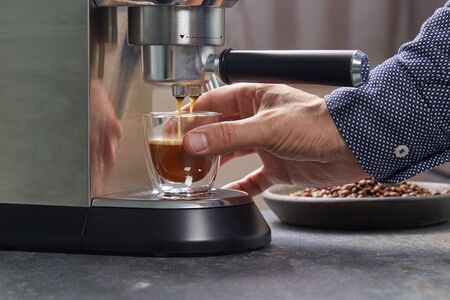 Freshly made espresso in a beautiful transparent double-circuit mug is on the coffee maker. Banque d'images - 130072187
