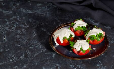 Tomato halves with finely chopped parsley in a sauce of sour cream and salt lie on a plate on a dark background. Healthy diet.