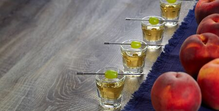 Shot of four servings of Grappa with grapes on skewers and ripe peaches on a blue napkin on the wooden surface of the table. Horizontal image. Stockfoto