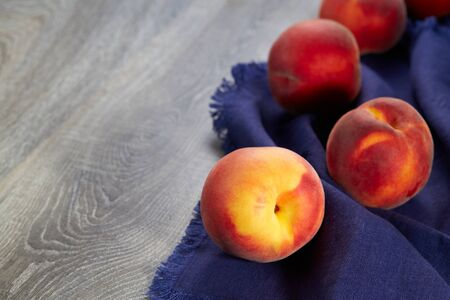 Lovely ripe peaches lie on a blue linen kitchen napkin on the table. Natural fruit.