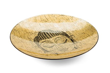 Buddhas face depicted on a gilded bamboo dish is isolated on a white background with shadows. Imagens