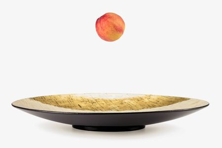 Large gilded inside dish is isolated on a white background with a ripe peach falling into it. Abstract image.