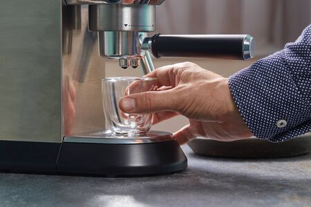 Hand installs beautiful little transparent espresso Cup under the holders household kitchen automatic coffee machine.