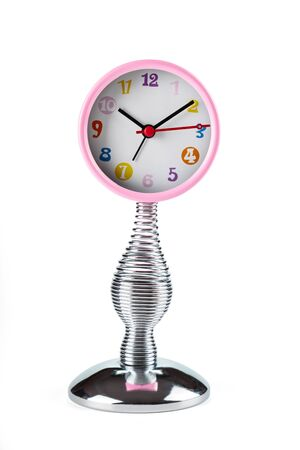 Pink clock with hands on a flexible spring. Front view. 스톡 콘텐츠
