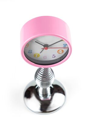 Pink clock with hands on a flexible spring. Top view.