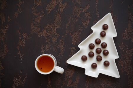 Christmas tree-shaped plate with cherry candies and a Cup of tea on a dark brown background. Copy space. Фото со стока