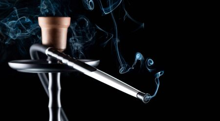 Hookah, from the mouthpiece of which curls a beautiful smoke on a black background.