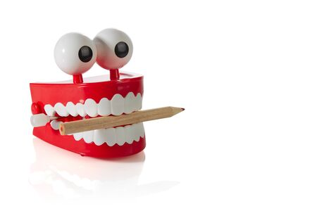 Clockwork jaw toy with sharpened pencil in teeth isolated on white background. Concept: gnawing knowledge. 스톡 콘텐츠