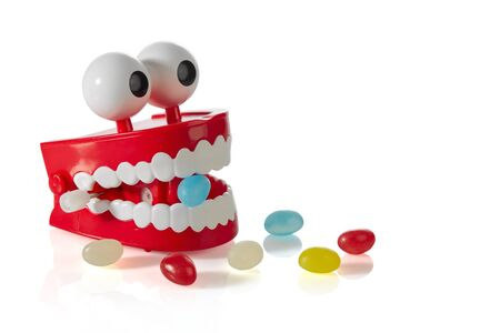 Clockwork jaw toy with a blue Lollipop in its teeth and scattered randomly colored candies isolated on a white background with shadows. Free space for your text. 스톡 콘텐츠