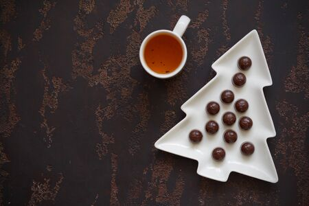 Christmas tree-shaped plate with cherry candies and a Cup of tea on a dark brown background. Top view. Free space for your text.