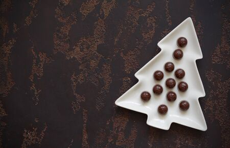 Christmas tree-shaped plate with cherry-filled chocolates on a dark brown background.