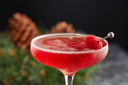 Glass of pink Spumante close - up with raspberries on a steel skewer on the background of a Christmas wreath with cones.