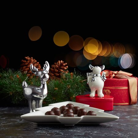 Christmas still life with sweets and gifts on a dark background.